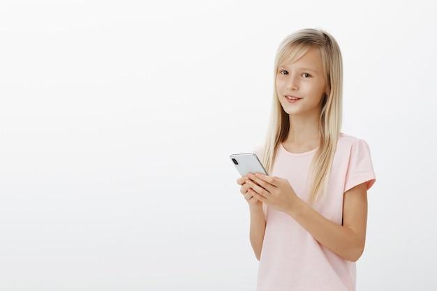La ragazza può usare i gadget meglio dei genitori. ritratto di fiducioso adorabile bambino in giovane età con begli occhi in maglietta rosa, tenendo lo smartphone e sorridente Foto Gratuite