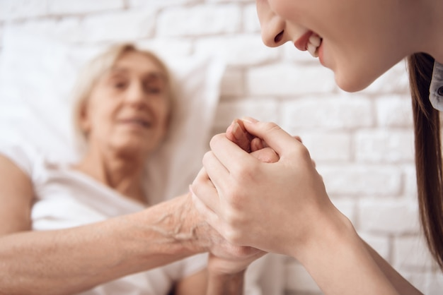 Girl care elderly woman in bed at home Premium Photo