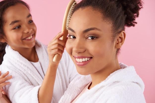 Girl carefully combing mother's hair. Premium Photo