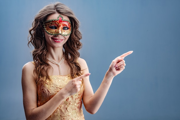 The girl in the carnival mask is smiling while standing and pointing to the side Premium Photo