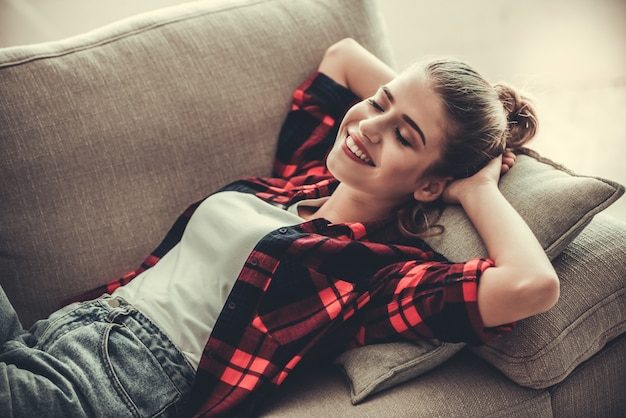 Girl in casual clothes is smiling while lying on couch. Premium Photo