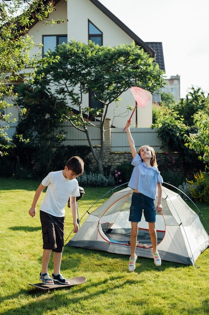 Girl catching butterflies with scoop net and boy playing skateboard near tent camp Free Photo