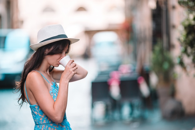 Girl caucasian drinking hot drink coffee walking in street at europe Premium Photo