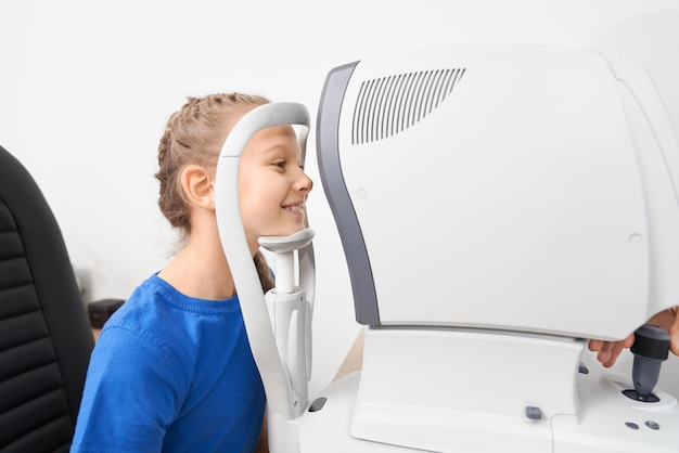 Girl checking eye vision with ophthalmologic equipment Premium Photo