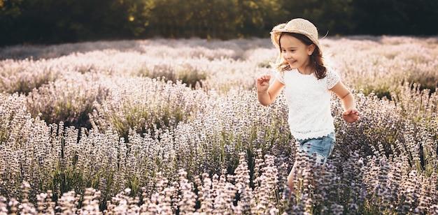 晴れた夏の日にラベンダー畑を応援して走っている女の子 Premium写真
