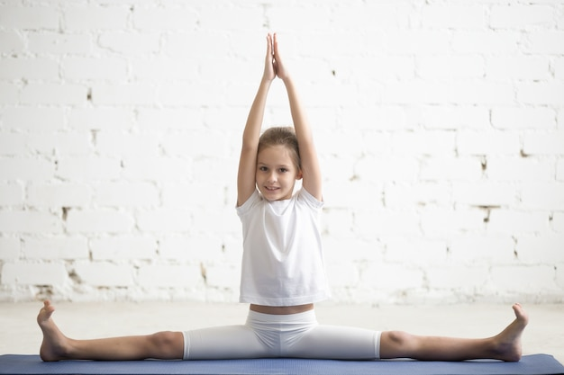 Girl child in samakonasana pose, white studio background Free Photo