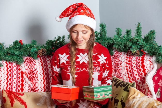 Girl choosing from two christmas gift boxes in new year's holidays decorations Premium Photo
