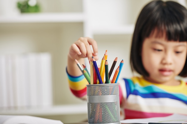 Девушка выбирает карандаш для рисования Premium Фотографии