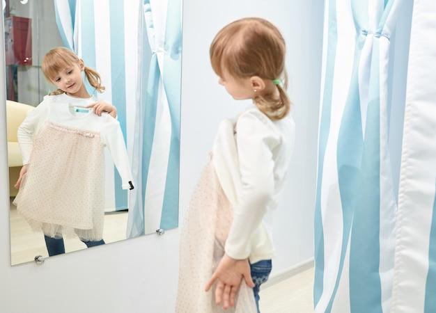 소녀 선택, 쇼핑몰에서 드레스를 시도 하 고 거울을보고. 무료 사진