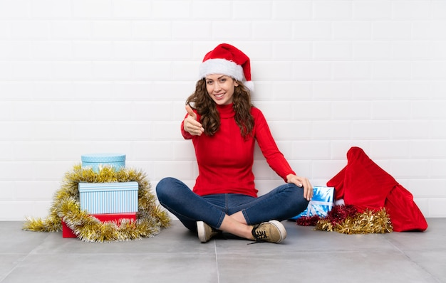 Girl in christmas holidays sitting on the floor handshaking after good deal Premium Photo