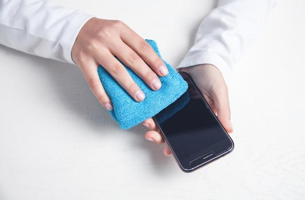 オフィスでスマートフォンを掃除する女の子。 Premium写真