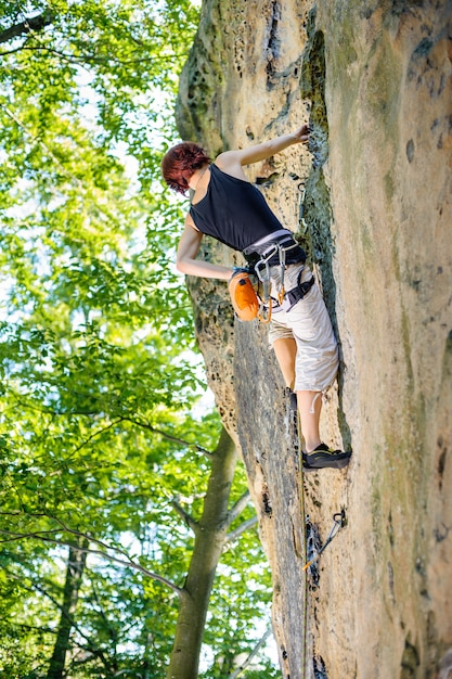Girl climber climbing with rope and carbines on big boulder Premium Photo