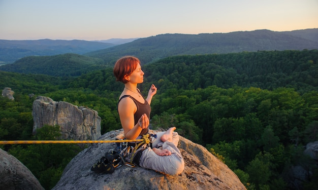 Girl climber sitting secured with rope and meditating with crossed legs on high mountain summit Premium Photo