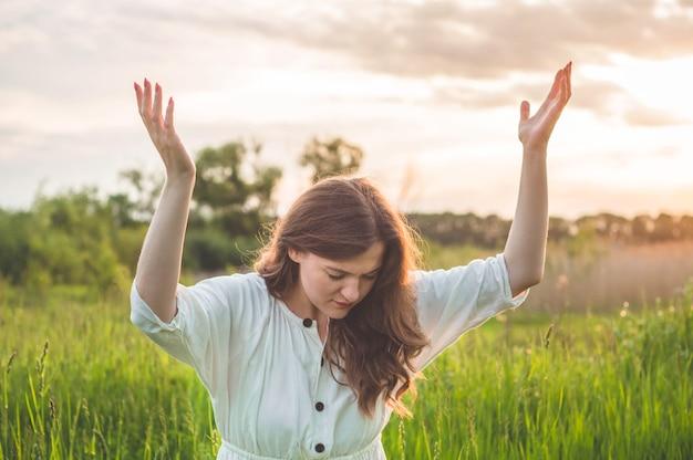 美しい日没時にフィールドで祈る少女は目を閉じた Premium写真