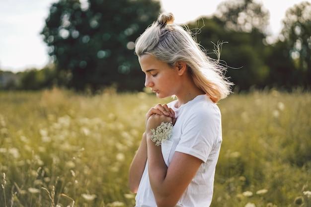 女の子はフィールドで祈りながら目を閉じた。信仰のための祈りの概念に折り畳まれた手 Premium写真