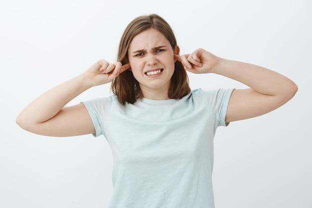 Девушка закрывает уши, чувствуя недовольство, когда рядом с ней дерутся люди. сильно недовольная молодая женщина стискивает зубы из-за дискомфорта, чувство беспокоит из-за громкого звука, прикрывающего слух затычками для ушей Бесплатные Фотографии
