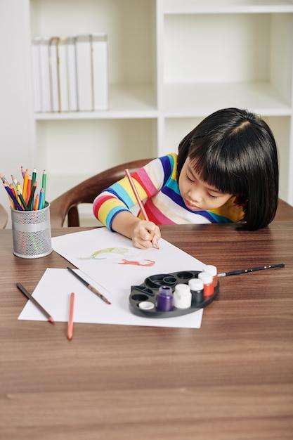 Девушка сосредоточилась на рисовании Premium Фотографии