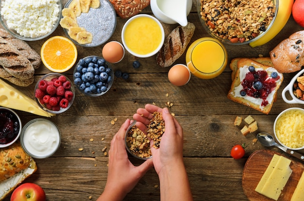 Girl cooking breakfast - granola with yogurt, fruits, berries, milk, yogurt, juice, cheese. clean eating, dieting, detox, vegetarian food concept Premium Photo