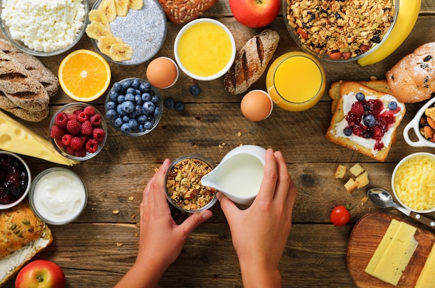 Girl cooking breakfast - granola with yogurt, fruits, berries, milk, yogurt, juice, cheese. clean eating, dieting, detox, vegetarian food concept. Premium Photo
