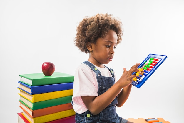 Girl counting on abacus in studio Free Photo