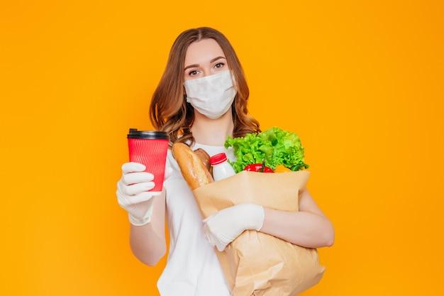 Девушка-волонтер-курьер в защитной маске держит бумажный пакет с продуктами, овощами, травами, показывает чашку кофе, изолированную над желтой стеной, карантин, коронавирус, безопасная еда, доставка онлайн Premium Фотографии