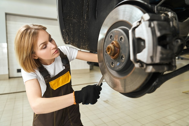 Girl in coveralls fixing car brake disk, using tool. Free Photo