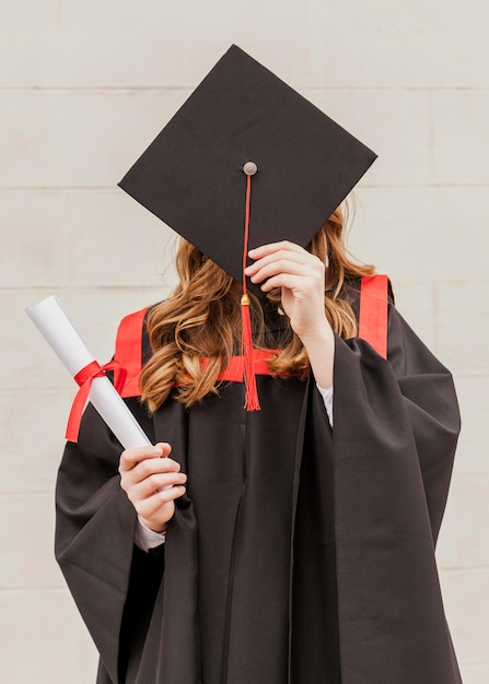 Девушка закрыла лицо выпускной шляпой Premium Фотографии