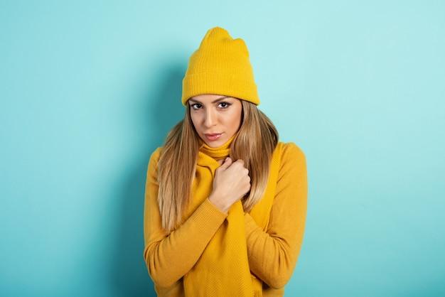 女の子は風邪をひかないように身を隠す。シアンの背景 Premium写真