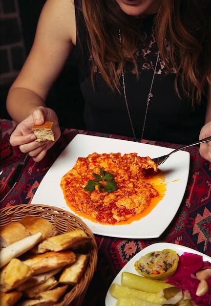 女の子、menemenを食べる顧客、玉ねぎとトマトのトルコ式朝食オムレツ。 無料写真
