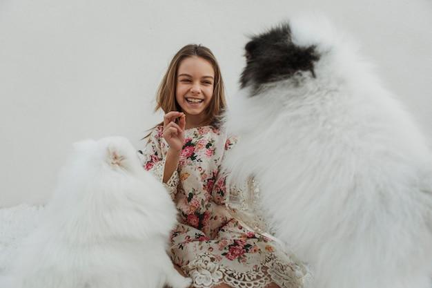 Ragazza e simpatici cuccioli bianchi che giocano a prendere Foto Gratuite
