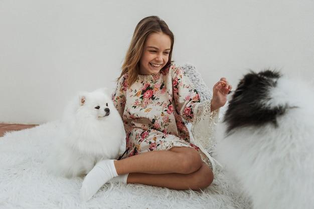 Ragazza e simpatici cuccioli bianchi Foto Gratuite