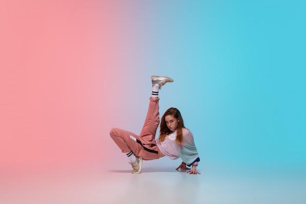 Девушка танцует хип-хоп в стильной одежде на градиентный фон в танцевальном зале в неоновом свете. Бесплатные Фотографии
