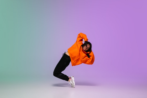 Girl Dancing Hip Hop In Stylish Clothes On Gradient Background At Dance Hall In Neon Light Free Photo