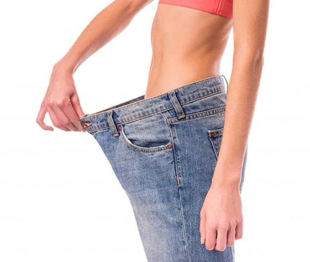 Girl demonstration of their weight loss for example jeans. Premium Photo