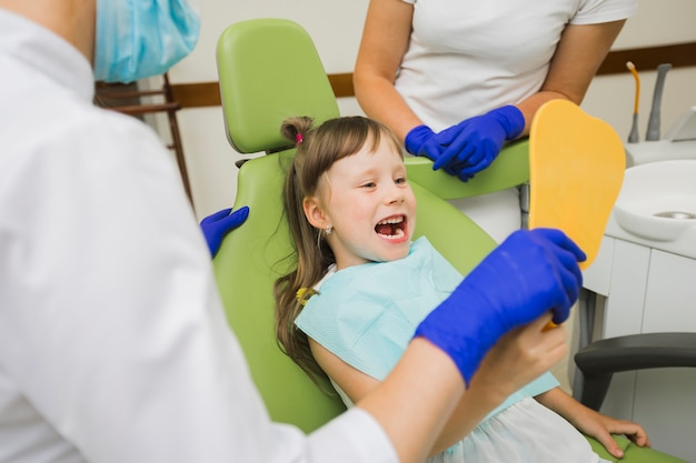 Girl at dentist looking in the mirror Free Photo