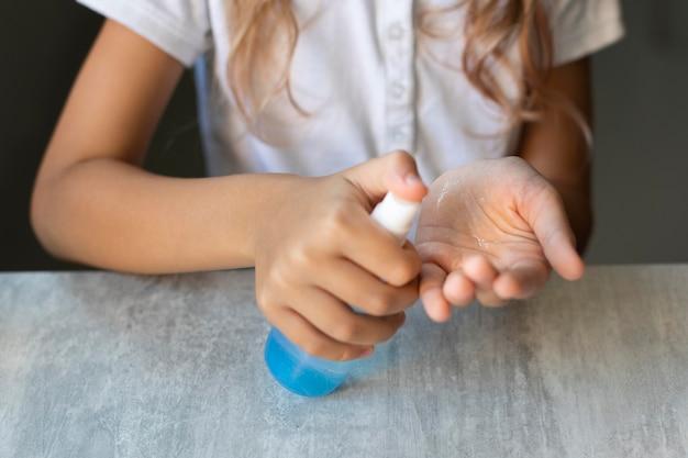 Девушка дезинфицирует руки, сидя за своим столом Бесплатные Фотографии