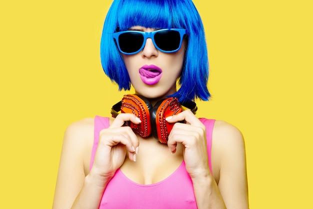 Девушка dj в солнцезащитных очках парика и розовом купальнике, слушая музыку в наушниках на желтом фоне. фото высокого качества Premium Фотографии