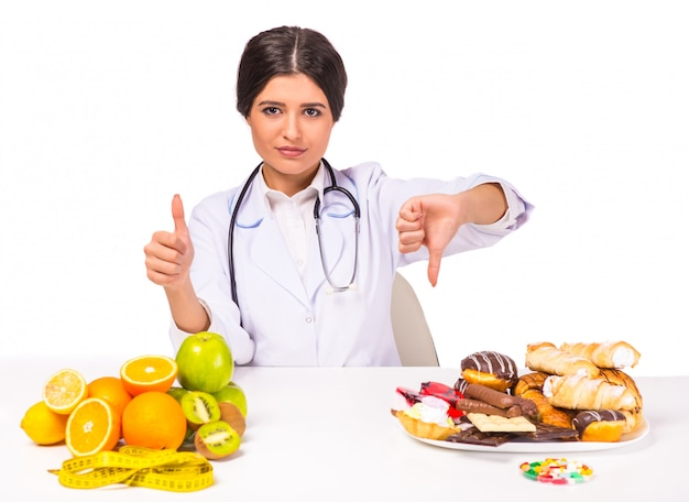Girl doctor is choice between healthy and unhealthy foods. Premium Photo
