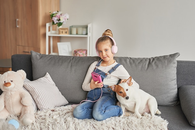 Girl and dog laying on couch in headphones, listening to music with her smarthphone Premium Photo