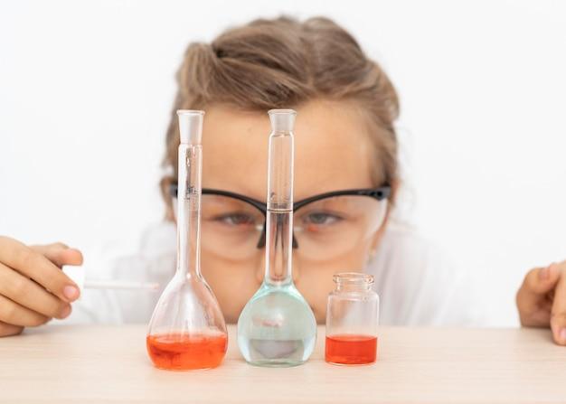 試験管で化学実験をしている女の子 無料写真