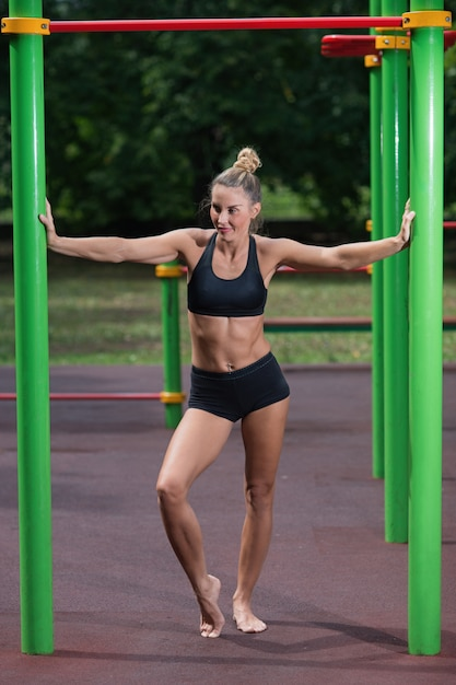 Girl doing exercises on the horizontal bar. the woman is engaged in workout Premium Photo