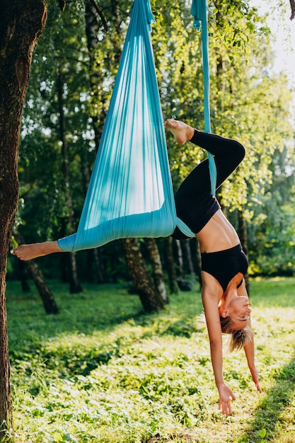 Girl doing fly yoga at the tree outdoors. Premium Photo