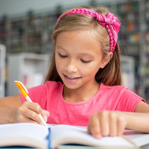 Девушка делает домашнее задание в библиотеке Бесплатные Фотографии