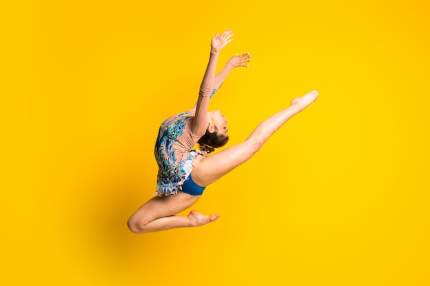 Girl doing rhythmic gymnastics jumping Premium Photo