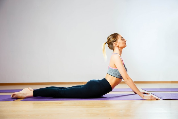 Girl doing warming up exercise for spine, backbend, arching stretching her back working in yoga class. Premium Photo