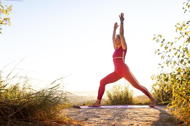 日の出のスポーツマットの上で2つの手をヨガの練習をしている女の子 Premium写真