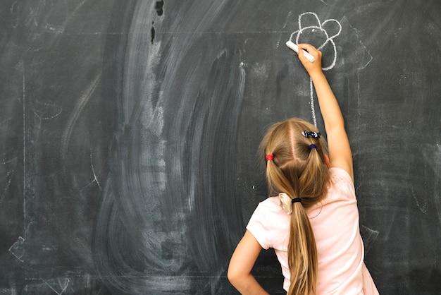 Girl drawing on blackboard Free Photo