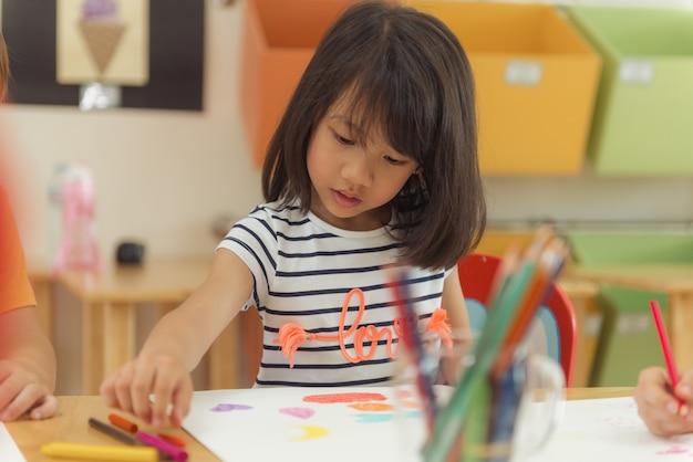 유치원 교실, 유치원 및 아이 교육 개념, 빈티지 효과 스타일 사진에서 컬러 연필 드로잉 소녀. 무료 사진