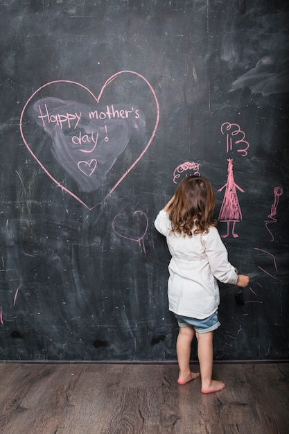 Girl drawing near happy mothers day inscription Free Photo