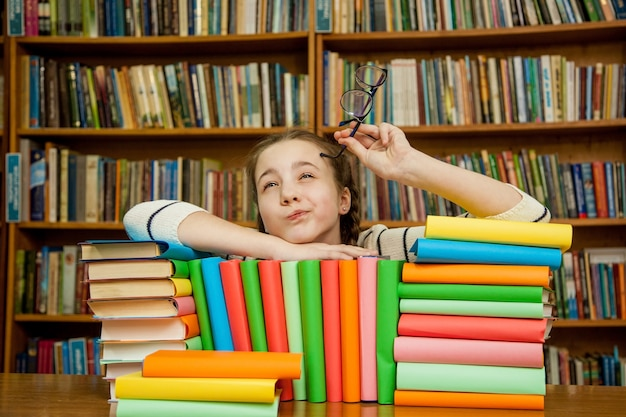 Girl dreams with books in the library. Premium Photo